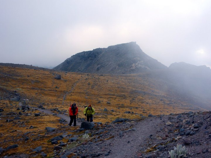 Crossing a bleak plateau beneath Carihuairazo, with Pointless Peak behind