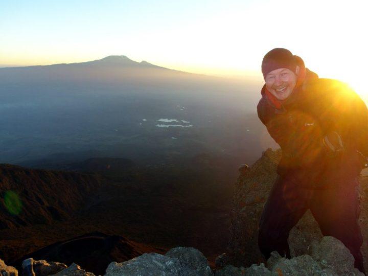 On the summit of Mount Meru, with Kilimanjaro on the horizon behind