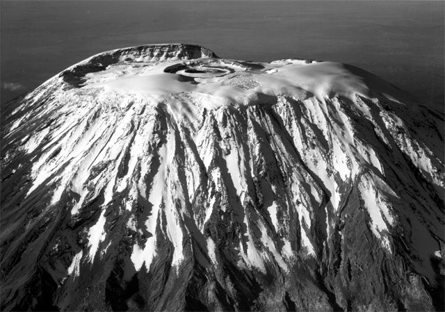 The snow-capped summit of Kilimanjaro containing the nearly perfect crater is flanked by deep furrows of lava flow and glacial erosion, 1938 (Photo: American Geographical Society / Wikimedia Commons)