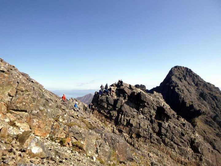 Hikers on Am Basteir's Bad Step, with Sgurr nan Gillean behind