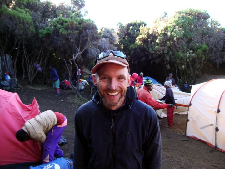 Dr Jeremy Windsor looking happy among the mountains at camp on Kilimanjaro (Photo: Jeremy Windsor)