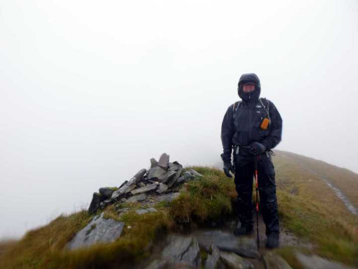 At the innocuous summit cairn on Sgurr Choinnich Mor. The orange camera is waterproof, but the phone in my right pocket was not.