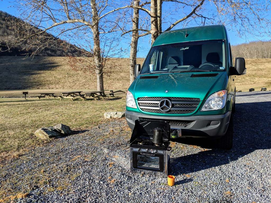 van in campground parking lot with stove in front