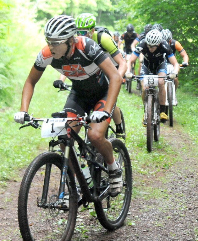 Cole House (1) winner of the 20015 Ore to Shore Hard Rock 48-mile race makes his way up the Lucy Hill Luge Track in Negaunee, MI, Saturday, August 8, 2015. (photo by Ron Caspi)
