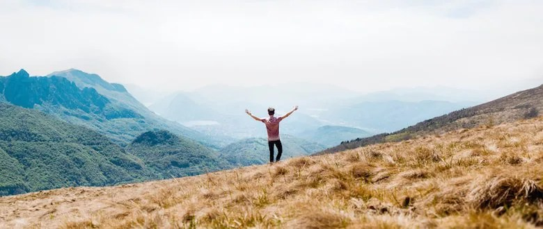 Man Standing on top of a mountain with his hands raised