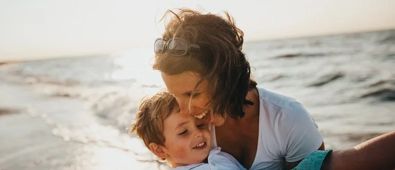 Mother and son laughing on the beach