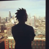 Man staring out window with mohawk