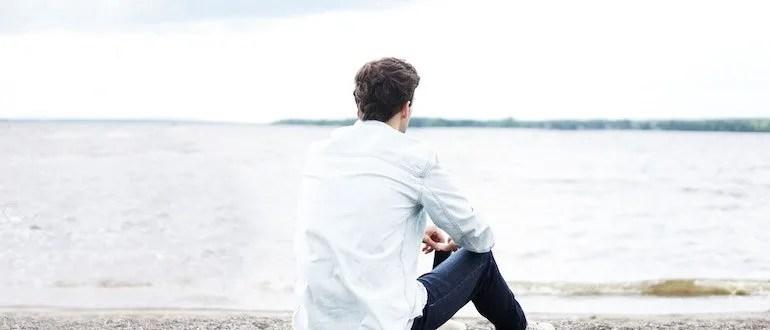 Man sitting on beach looking at ocean