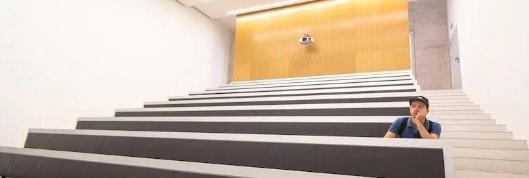 Man sitting alone in empty classroom