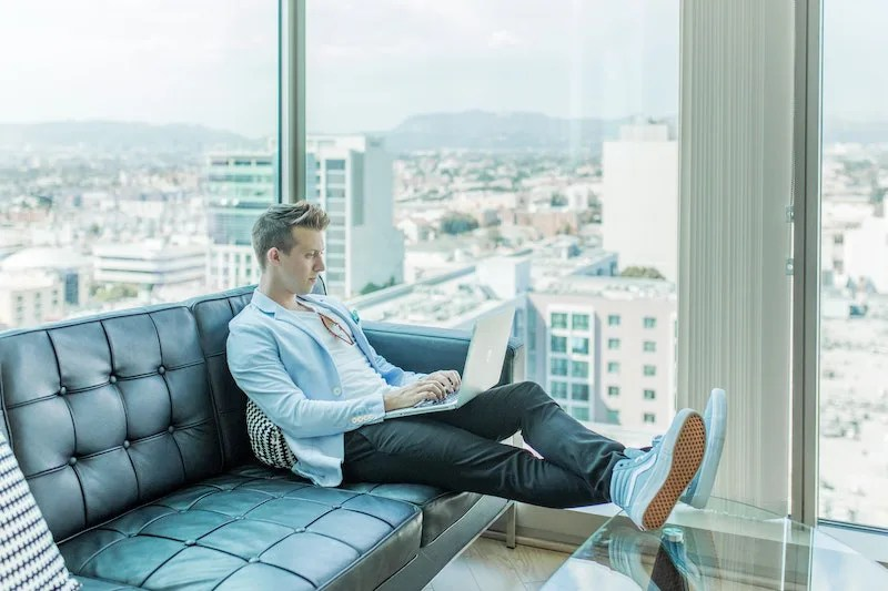 Man sitting on modern couch with laptop