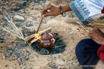 Traditional moroccan teapot in fire. Tea preparation in the desert.