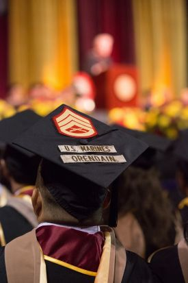 "A photograph of students graduating at USC with one student in particular who is in focus, where their graduation cap has the USMC Rank of sergeant and the words ""U.S. Marines Orendain"""