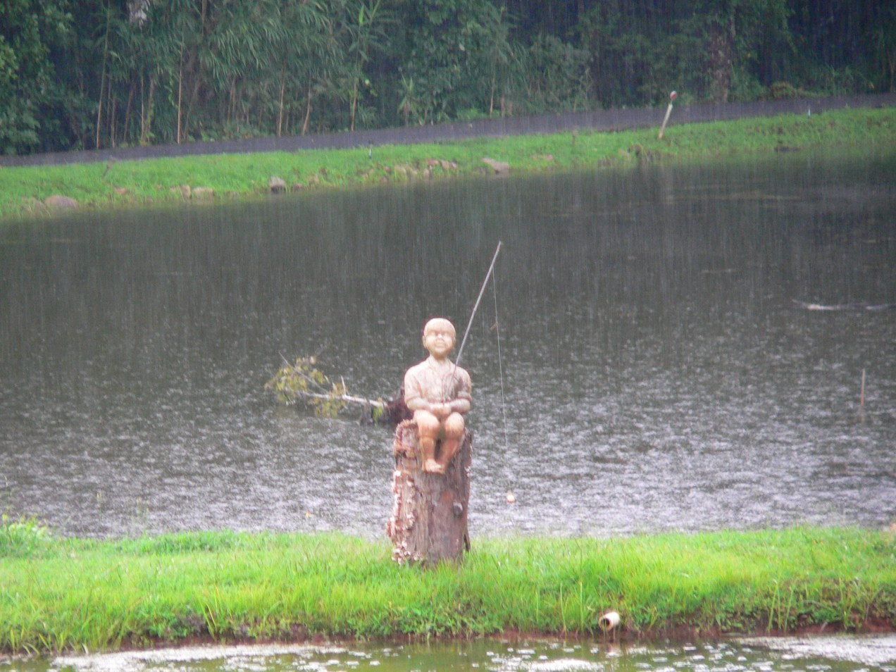 This little boy likes to fish rain or shine, all the time.