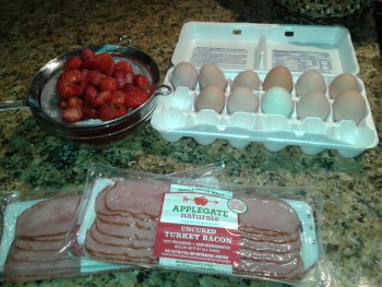 Defrosted strawberries, eggs in a carton and packaged bacon.