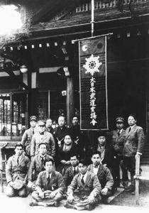 Foto di gruppo scattata ad Ayabe nel 1932 sotto la bandiera del Budo Sen'yokai. Nella seconda fila a sinistra, in piedi: Morihei Ueshiba, Sumiko Deguchi, Onisaburo Deguchi. Seduta tra Onisaburo e sua moglie, la nipote di Ueshiba, Yoichiro Inoue.