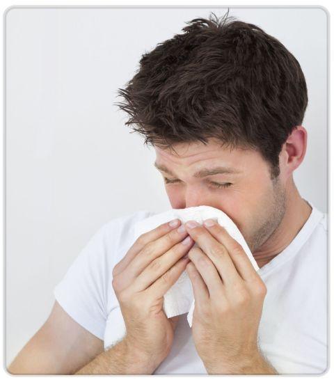 uomo che starnutisce a causa di un'allergia