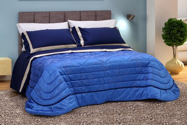 Coordinato letto composto da trapunta damasco blu e lenzuola balzate