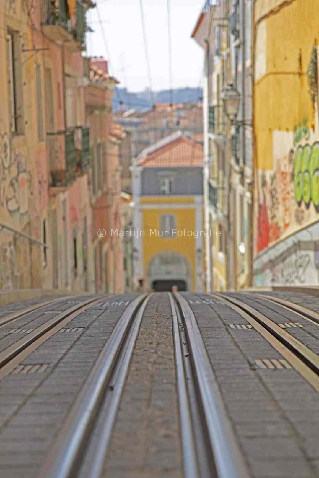 tramrails met gekleurde huizen in Lissabon, reisfotografie