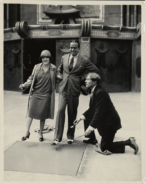 Mary Pickford and Douglas Fairbanks making history by having their footprints and handprints immortalized in cement outside Grauman's Chinese Theater with Sid Grauman on April 30, 1927