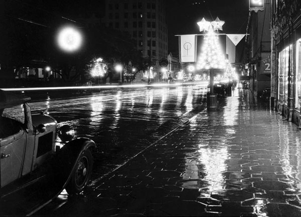 Circa 1935 view of a wet Hollywood Boulevard decorated for the holidays