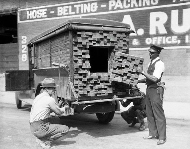 "Alerted by the smell of a broken bottle of liquor, Federal Agents inspect a ""lumber truck"". Los Angeles, 1926, Prohibition"