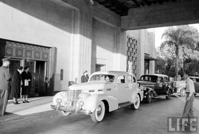 Cars pulling up at the front entrance of Bullocks Wilshire department store 1938