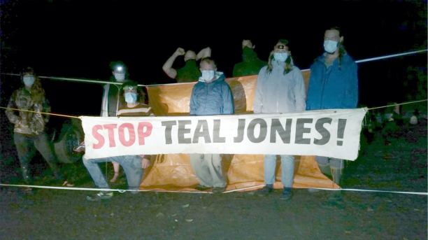 "fairy creek blockade protestors in front of ""stop teal jones"" sign"