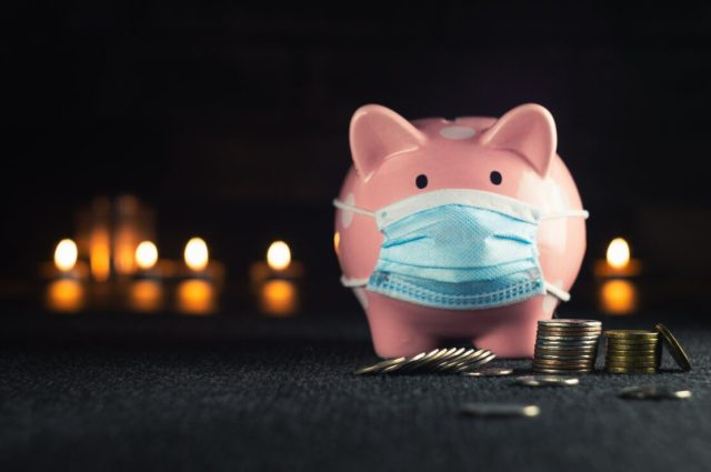 Budgeting, stock photo of a piggy bank with coins and a mask