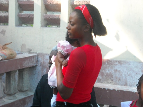 A young Haitian girl and baby