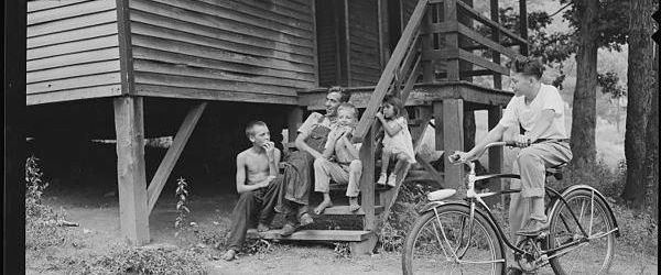 Miner and children sit on steps of company house.