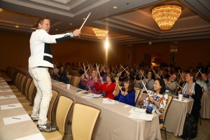 Marvelless Mark standing on top of 2 chairs in the front row revving up the energy for his audience in Las Vegas.