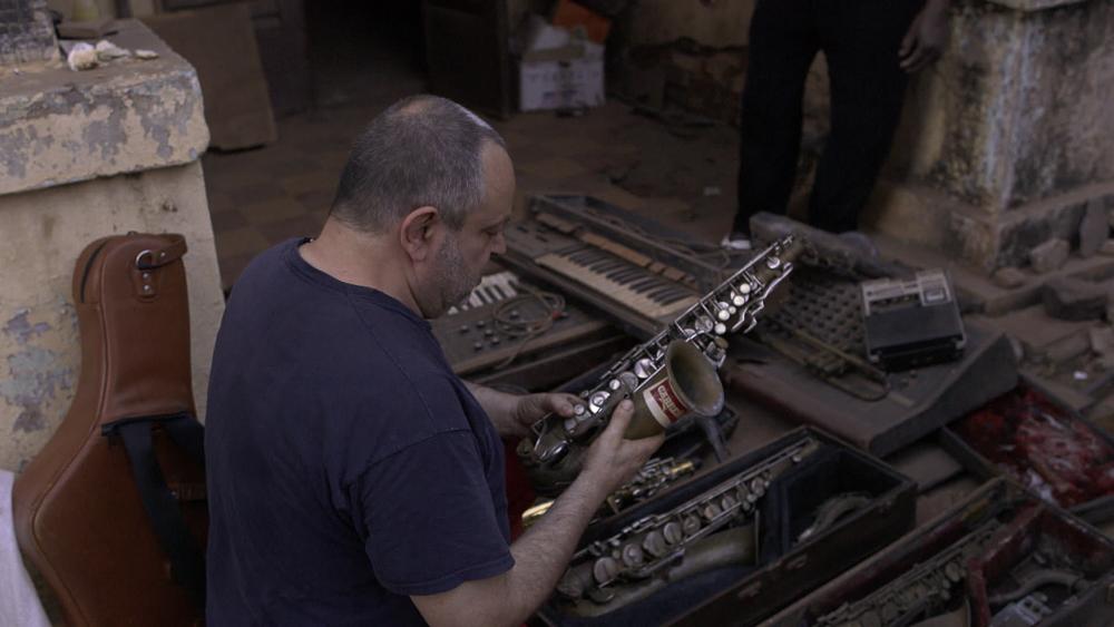 Saxofonist Georg Pfister betrachtet ein altes Saxofon der Railband
