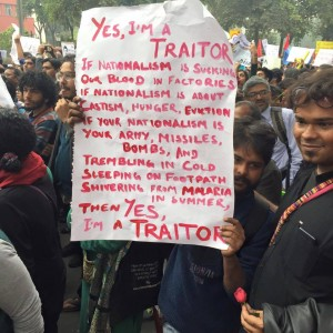 student holding I'm a Traitor playcard in JNU protest