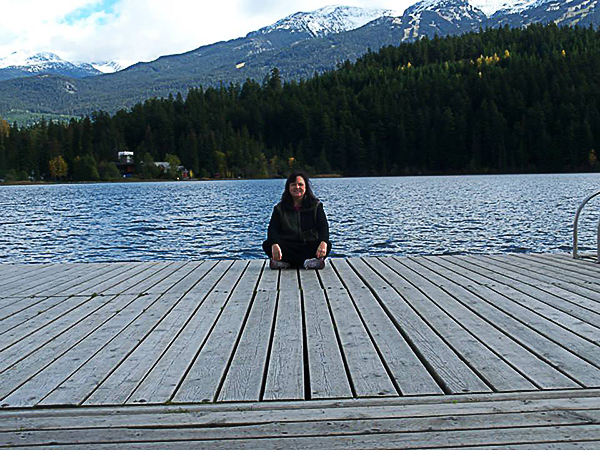 Reverend Marya OMalley meditating on mountain lakeside dock