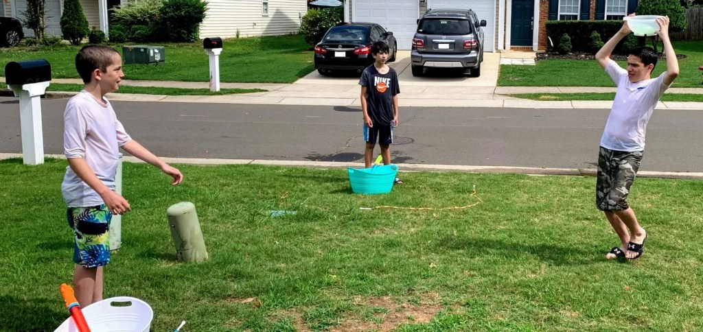 """Create a social distance """"dunking booth"""" using water balloon and a kitchen colander."""