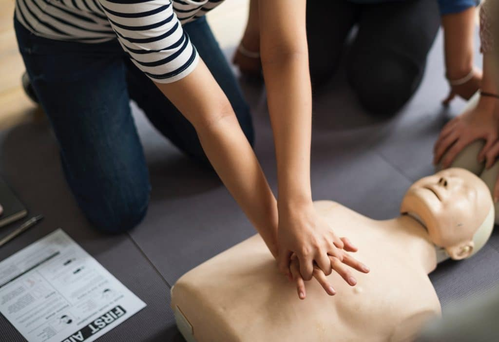 woman doing CPR on mannequin