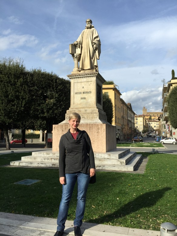 Sarah in front of the statue of Guido Monaco