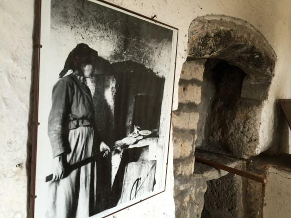 Picture of a woman putting matzoh in the oven beside the actual oven