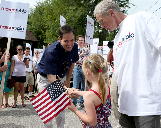 Republican presidential candidate Sen. Marco Rubio, R-Fla., shakes hands with Nellie MacDonald, 7, of Deering, N.H., as her father Gordon looks on before the 4th of July parade, Saturday, July 4, 2015, in Wolfeboro, N.H.