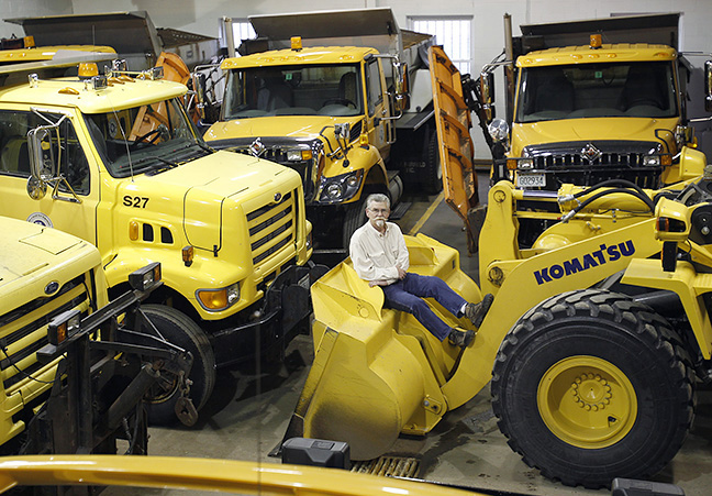 Salem Director of Public Works Rick Russell lounges on the front of the scoop on a new front loader in the Public Works garage in Salem. The trucks haven't had much use in the quiet leadup to winter.