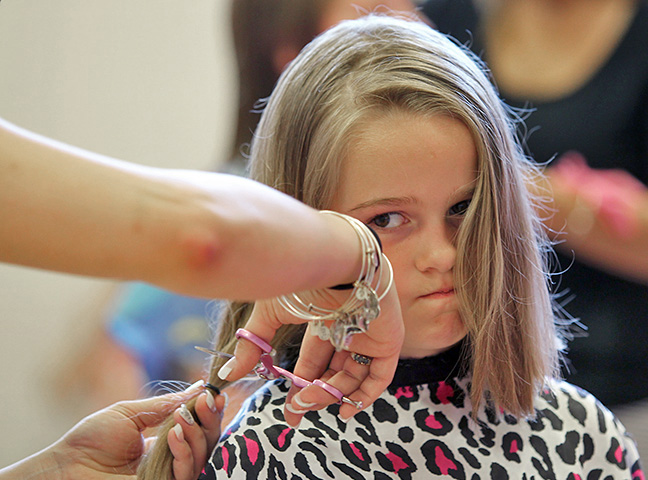 Cori McMeniman, 5, of Hampstead, reacts as she lose her locks during a Pantene Cut-at-thon at the Central School in Hampstead.