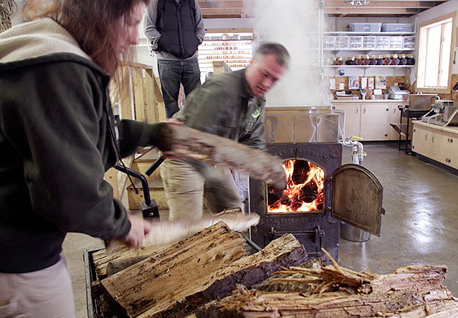 Kathy Gallagher and Paul Boulanger stoke the fire in their sugar house before a day of tours at their home.