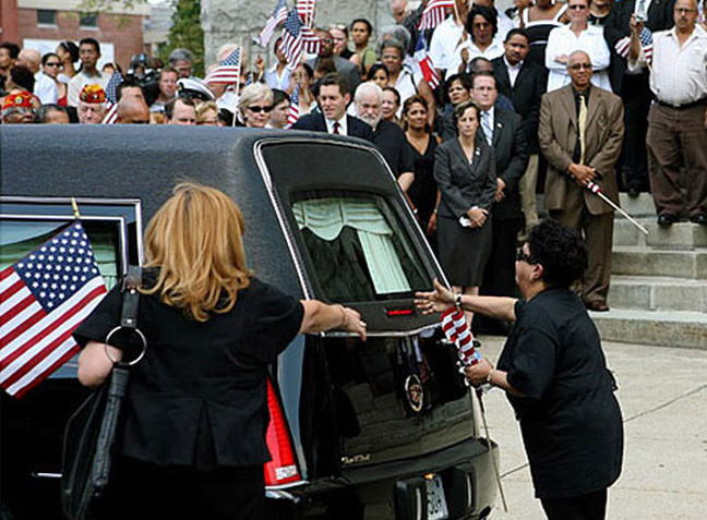 A family member reaches out to the hearse after the remains of Staff Sgt. Alex Jimenez were placed inside following a Mass at St. Mary's of the Assumption Church in Lawrence, Mass.