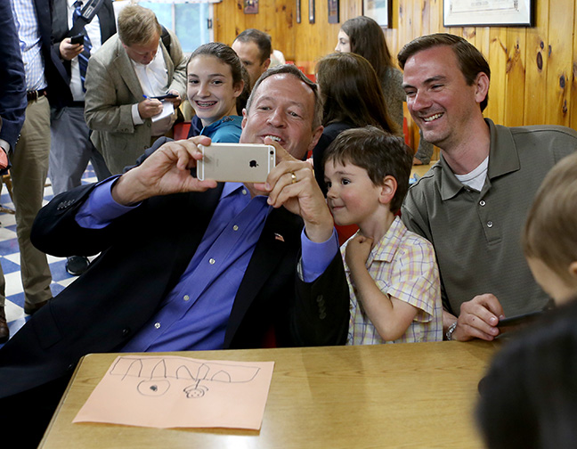 Former Maryland Gov. Martin O'Malley, left, takes a selfie with Harrison Adamec, 5, and his dad Shaun, of Framingham, Mass., during a campaign stop at Goldenrod Drive-in Restaurant, Sunday, May 31, 2015, in Manchester, N.H.