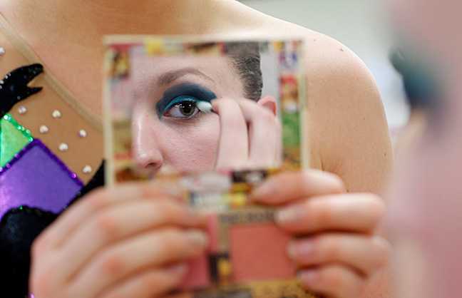 A teammate holds a mirror for Laura Schmidt has she puts on her eye shadow. Photo by Mary Schwalm.