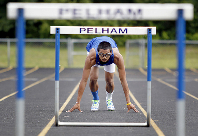 Pelham track standout Kevin Cheam poses for a photo through hurdles at Pelham high school.