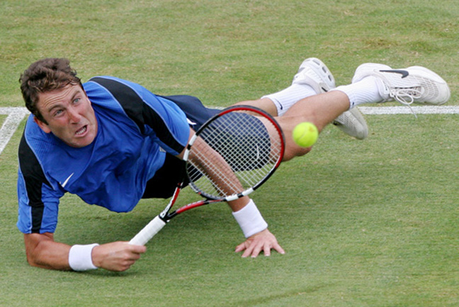 Justin Gimelstob dives for a return on the grass during a tennis match at the International Tennis Hall of Fame in Newport, R.I.