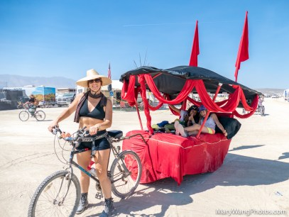 Bicycle towing a red covered bed