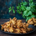 Crispy Onion Pakoda served on a black plate along with baked pakodas.