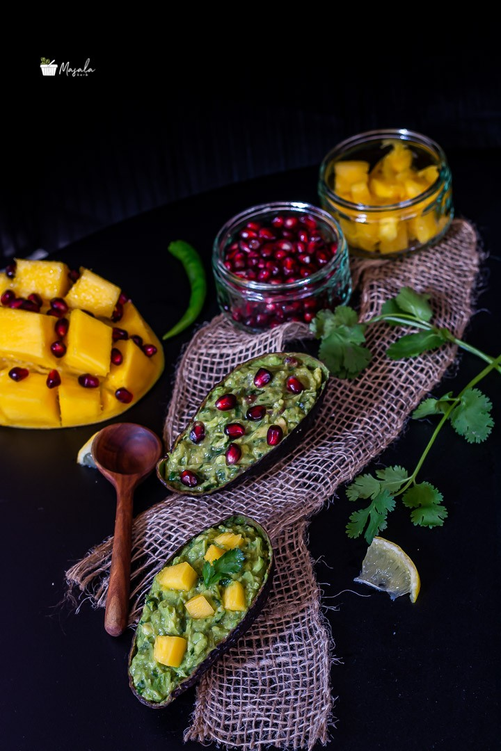 Cut mango and pomegranate arils with guacamole and Mango Pomegranate Guacamole in frame.